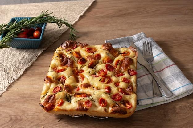 Focaccia com alecrim, azeite e tomate na mesa de madeira.