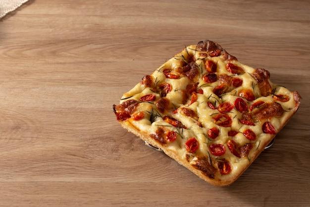 Focaccia com alecrim e azeite e tomate em mesa de madeira