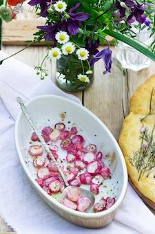 Focaccia com cebola, rabanete assado e um buquê de flores em uma mesa de madeira