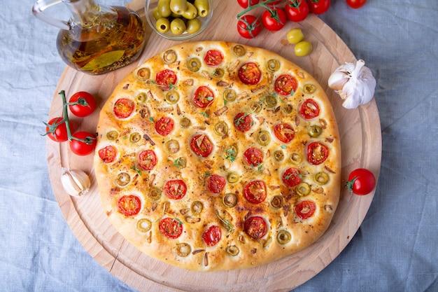 Focaccia com tomates e azeitonas. pão italiano tradicional. cozimento caseiro. close-up, foco seletivo.