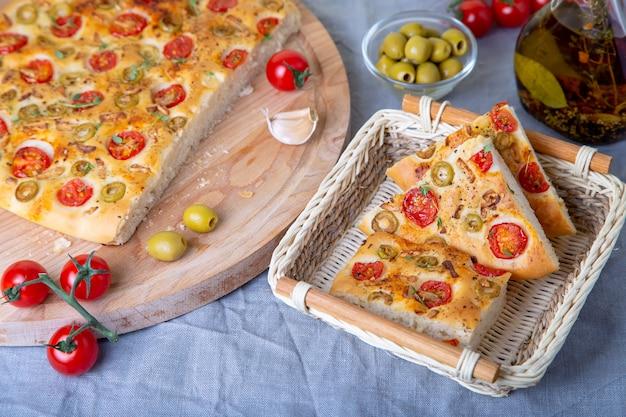 Focaccia com tomates e azeitonas. pão italiano tradicional. cozimento caseiro.