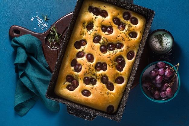 Focaccia com uvas vermelhas sobre uma mesa azul.