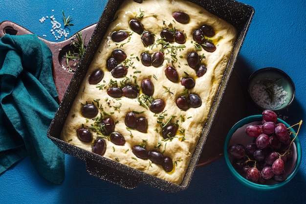 Focaccia crua com uvas vermelhas em uma mesa azul em uma assadeira.