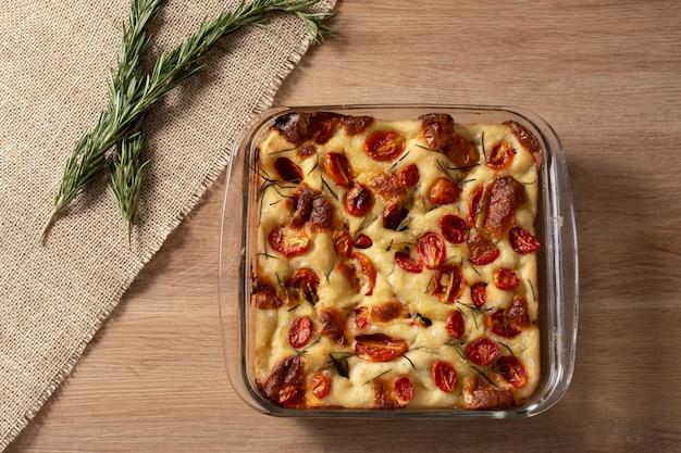 Focaccia de pugliese italiana caseira com alecrim, azeite e tomate na mesa de madeira.