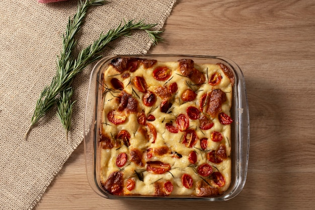 Focaccia de pugliese italiana caseira com alecrim, azeite e tomate na mesa de madeira