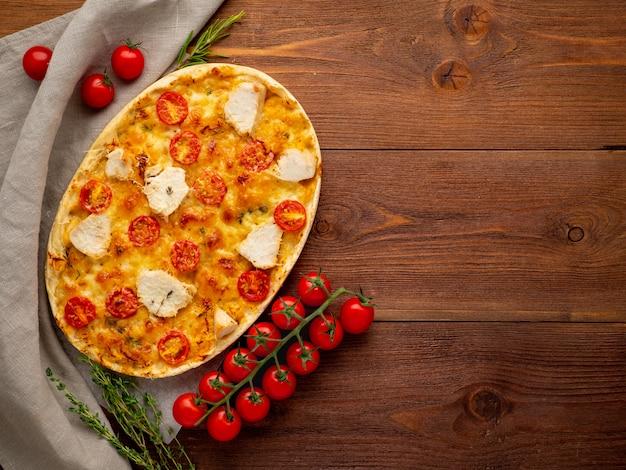 Focaccia dourada apetitosa com tomate, carne de frango, especiarias na mesa rústica de madeira escura