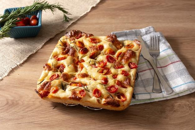 Focaccia italiana artesanal de pugliese com alecrim, azeite e tomate sobre madeira