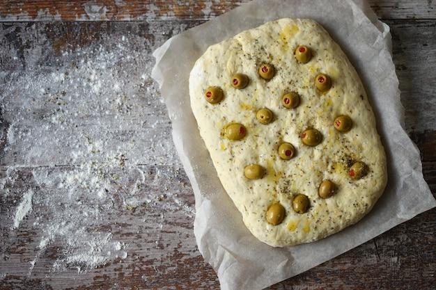Focaccia italiana com azeitonas antes de assar.