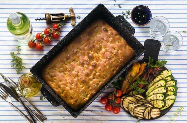 Focaccia italiana e legumes grelhados em uma mesa com vinho tinto e ervas aromáticas. menu de verão