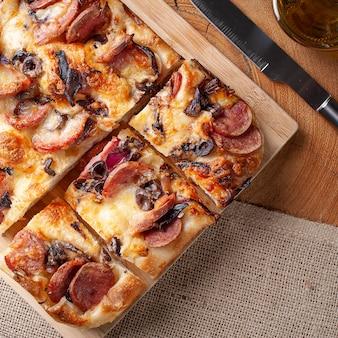 Focaccia italiana tradicional com linguiça calabresa, azeitonas pretas, queijo parmesão e cebola - pão achatado caseiro focaccia. vista do topo