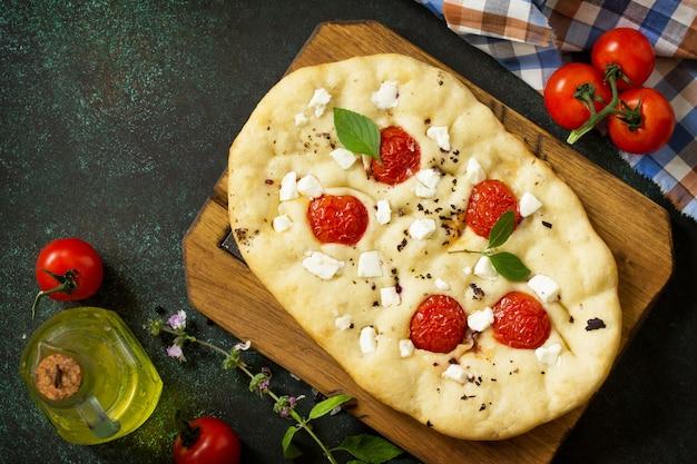 Focaccia italiana tradicional com tomate alecrim e focaccia de pão achatado caseiro feta