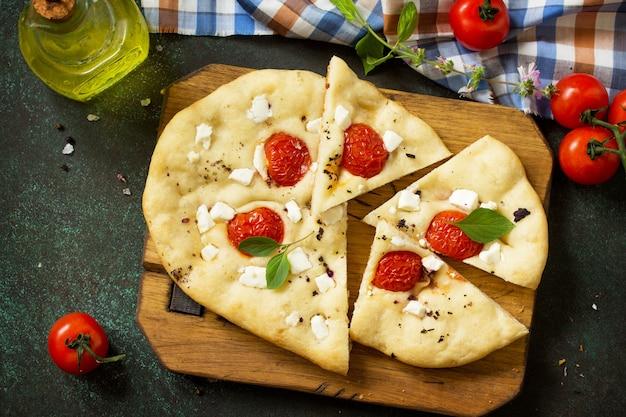Focaccia italiana tradicional com tomate alecrim e queijo feta vista de cima plano de fundo