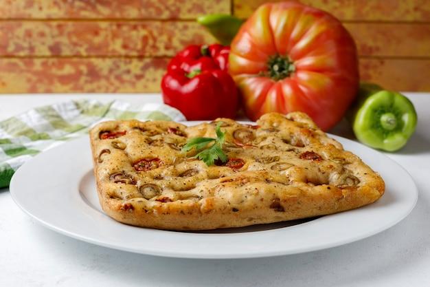 Focaccia italiana tradicional com tomate e azeitonas