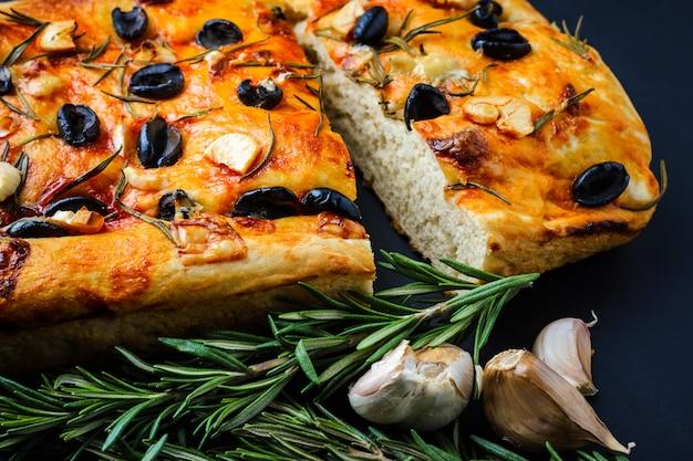 Focaccia italiano com alecrim e azeitonas em uma mesa de madeira.
