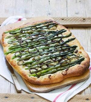 Focaccia ou pizza com aspargos, cebolas, azeitonas e ervas