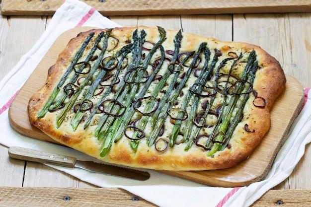 Focaccia ou pizza com espargos, cebolas, azeitonas e ervas. estilo rústico, foco seletivo.