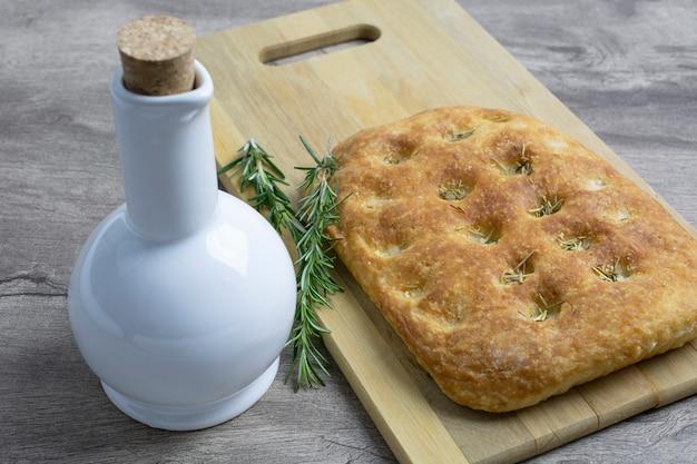 Focaccia sal e alecrim sobre placa de madeira com garrafa de azeite