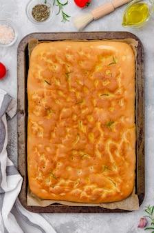 Focaccia tradicional italiana fresca cozida com alecrim, alho, sal marinho e azeite em um fundo cinza de concreto. vista do topo.