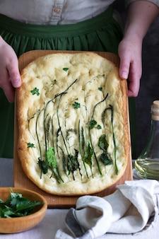 Focaccia vegana feita de massa de levedura com várias ervas mantidas por uma mulher. estilo rústico.