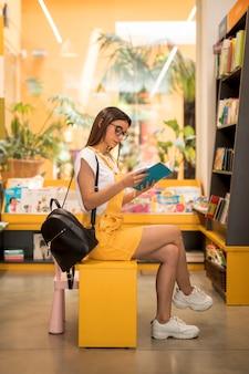 Focada adolescente colegial lendo livro no assento