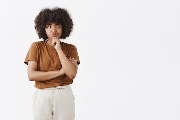 Focada e pensativa linda garota com penteado afro em camiseta marrom e calça sorrindo, olhando bem enquanto pensa com dúvidas
