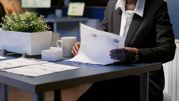 Focada empresária afro-americana a trabalhar horas extraordinárias na apresentação da gestão da empresa à noite na sala de reuniões do escritório. gerente executivo analisando a papelada do lucro financeiro
