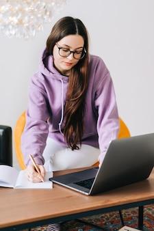 Focada estudante universitária jovem caucasiana em óculos, estudando com laptop, preparando-se para o exame de teste, escrevendo o ensaio fazendo lição de casa em casa, conceito de educação à distância.