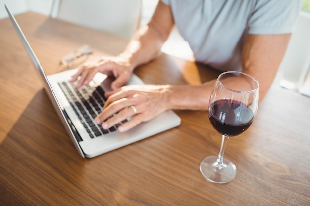 Focada homem sênior usando laptop e bebendo vinho em casa