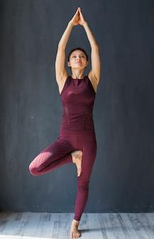 Focada mulher em pé em uma pose de árvore com os braços estendidos acima dela