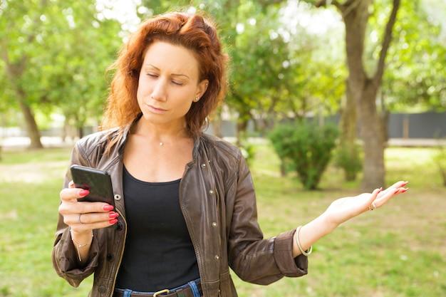 Focada mulher séria com smartphone lendo a mensagem
