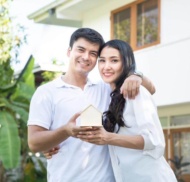 Focada na forma de madeira da casa nas mãos dos pares felizes asiáticos do lado de fora na frente da casa. conceito do negócio dos bens imobiliários e da propriedade.