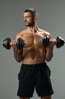 Focado adorável homem caucasiano em roupas esportivas levantando pesos isolados em fundo cinza