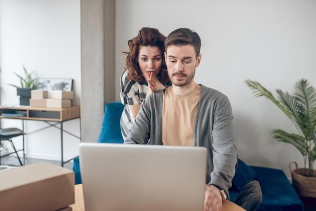 Focado bonito trabalhador de escritório masculino e sua colega surpresa olhando para a tela do laptop