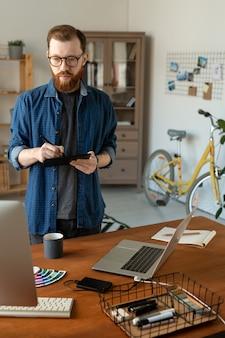 Focado criativo jovem designer gráfico com barba em pé na mesa e olhando para o monitor do computador enquanto trabalha com o digitalizador