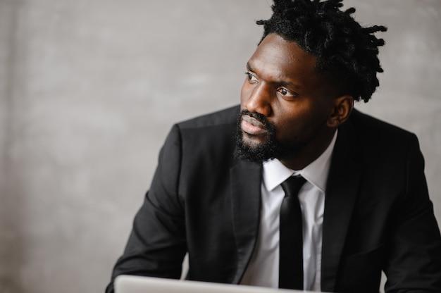 Focado empresário negro em terno, segurando vídeo chamada com clientes no laptop.