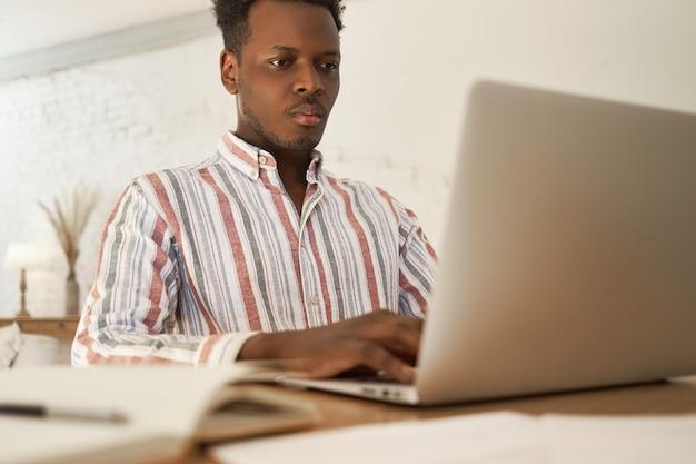 Focado jovem africano do sexo masculino fazendo tarefas remotas freelance em casa, procurando informações usando wi-fi de alta velocidade.