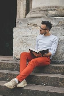 Focado na leitura de um livro de estudante perto de uma universidade