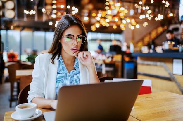 Focado na moda atraente shopaholic sentado no café e pesquisa on-line