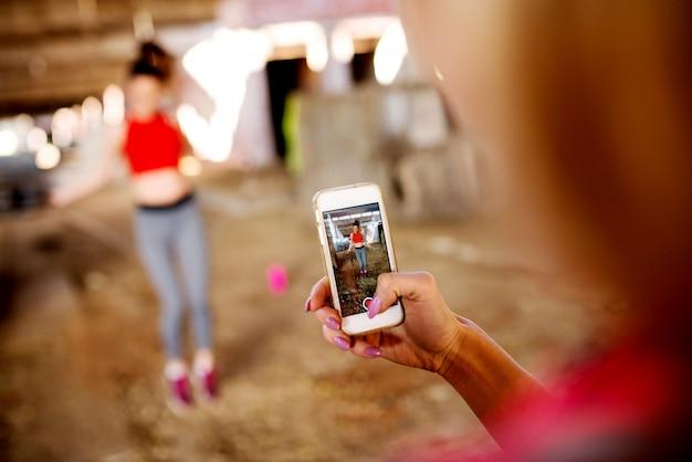 Focado no celular enquanto uma garota está gravando, outra garota está fazendo exercícios com pular corda.