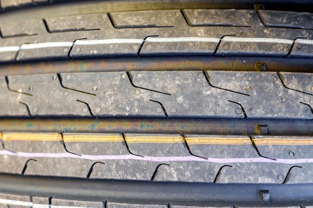 Focado no close up de pneus de carro novos com marcas de piso para boa tração.