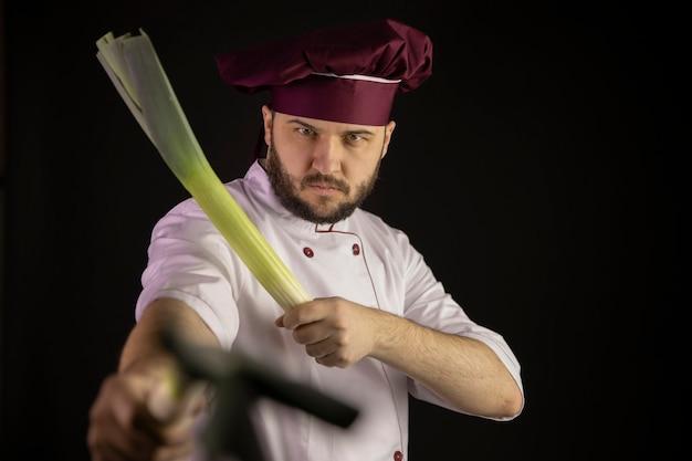 Focado no jovem chef barbudo masculino de uniforme, segurando cebolas de alface nas mãos, olhando para a câmera isolada no preto