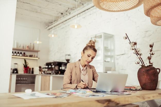 Focado no trabalho. belo designer inteligente desenhando novos esboços sentado sozinho à mesa.