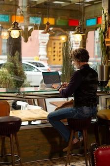 Focado no trabalho. homem adulto sério sentado no café perto da mesa da janela, trabalhando em seu laptop e bebendo café.