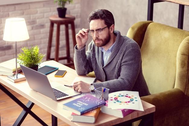 Focado no trabalho homem bonito e simpático consertando seus óculos enquanto se concentra em seu trabalho