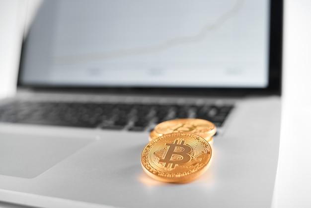 Foco afiado nos bitcoins dourados colocados no portátil de prata com carta financeira borrada em sua tela.