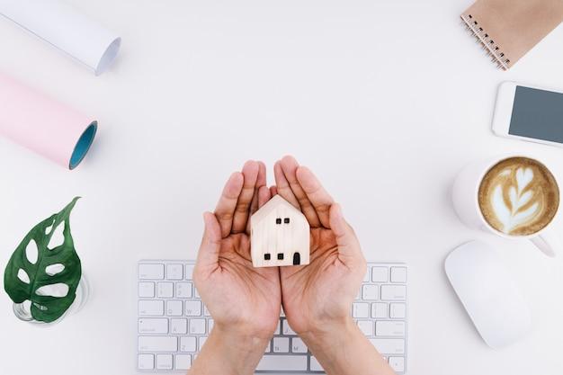 Foco da mão de uma mulher segurando uma mini casa de madeira na mesa de trabalho branca e inclui teclado, mouse, smartphone, notebook