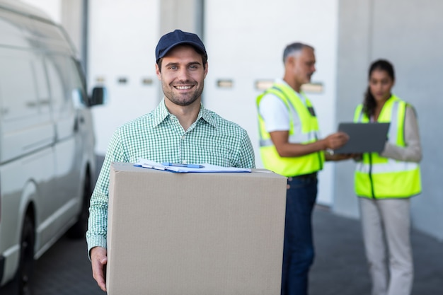Foco do entregador está segurando uma caixa de papelão e sorrindo para a câmera
