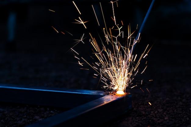 Foco do técnico no processo de soldadura na luz da faísca com equipamento.