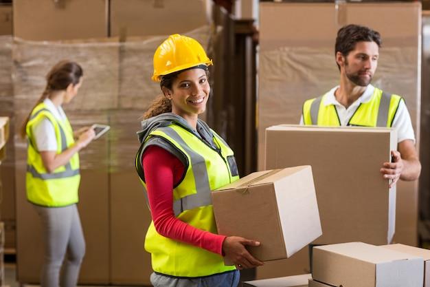 Foco do trabalhador está segurando mercadorias e sorrindo para a câmera