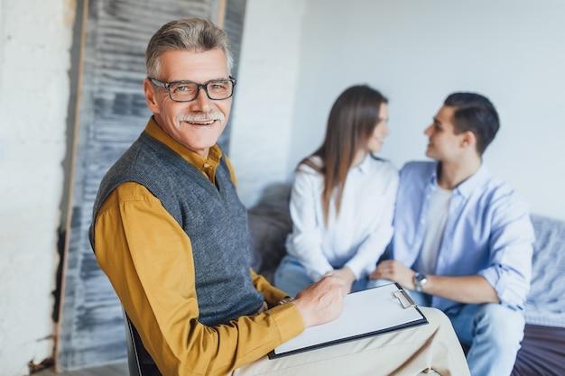 Foco em psicólogo feliz trabalhando com casal